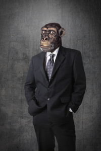 A nthropomorphous chimpanzee dressed and standing like a businessman