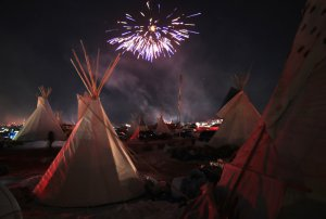 CANNON BALL, ND - DECEMBER 04:  Fireworks fill the night sky above Oceti Sakowin Camp as activists celebrate after learning an easement had been denied for the Dakota Access Pipeline near the edge of the Standing Rock Sioux Reservation on December 4, 2016 outside Cannon Ball, North Dakota. The US Army Corps of Engineers announced today that it will not grant an easement to the Dakota Access Pipeline to cross under a lake on the Sioux Tribes Standing Rock reservation, ending a  months-long standoff.  (Photo by Scott Olson/Getty Images)