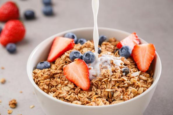 bowl-of-fortified-granola-or-muesli-cereal-with-strawberries-and-blueberries-with-soya-plant-milk-being-poured-on-top
